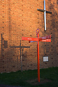 The cross on the wall of Herne Hill's United Reform Church and the direction sign post (plus its shadow) of Red Post Hill, south London. Echoed by a low winter sun, we see the three repeating crosses as a visual pun, a joke of three same shapes but with different meanings. The exterior of this church is from the 1970s period of architecture but the red post is a recent addition, instigated by locals to return the original landmark for this road junction, a marker for walkers and horses on old byways, paths and tracks going back many hundreds of years. On the post we see that Brixton is one mile away and the neighbouring areas of Herne Hill and Tulse Hill and Sydenham are close too.