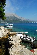 Rocks and boats, coastline of island of Korcula, Peljeski Kanal and Croatian mainland in background. Korcula old town, island of Korcula, Croatia
