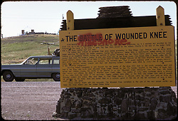 Wounded Knee, South Dakota. Signs signifying events that occured there in 1890 and updated by spray paint after the Incident at Wounded Knee in 1973, the year this photo was taken. The Wounded Knee Incident began February 27, 1973. The town of Wounded Knee was seized by followers of the American Indian Movement (AIM). The occupiers controlled the town for 71 days while United States Marshals Service and other law enforcement agencies cordoned off the town.