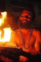India, Karnataka, Gokarna, 2006. A Keralan Hindu priest carries the symbolic birth fire backwards for over five miles to initiate the evening's prayers.