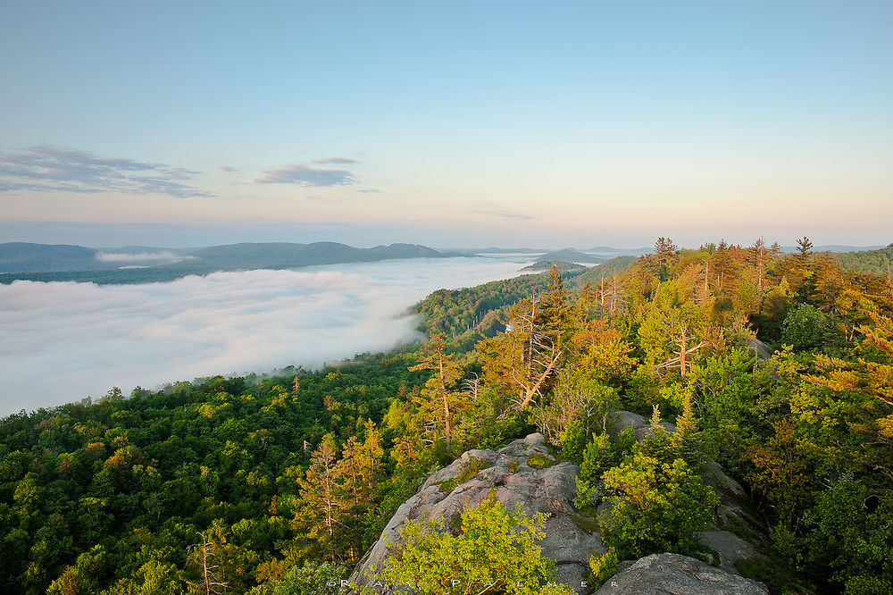 Bald Mountain, Adirondacks, NY.<br /> <br /> A little before sunrise, I climb the fire tower on Bald Mountain.  Below me, the narrow ridge that hosts me rises above the Fulton Chain Lakes, unseen beneath a sea of fog that is almost neatly held in a valley stretching to sight's end in either direction . Intent on capturing the sunrise on the opposite side of the tower cab, I fail one of the basic tenets of photography to always look behind you.  When I do, the south east view is side-lit, bathing my perch in golden light, kissing the tree tops below that, and skimming the top of the mist.  Fourth Lake lies under that subtly colored blanket, with decreasing numbers stretching into the downstream cloud.  It will burn off in the next half hour or so to reveal them like sparkling jewels.  There's much to be said for endless views, but for now I'll take the mystery of what lies beneath.