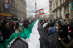 London, UK. 22nd May, 2021. Activists hold a huge Palestinian flag as tens of thousands of people take part in the National Demonstration for Palestine. It was organised by pro-Palestinian solidarity groups in protest against Israel's recent attacks on Gaza, its incursions at the Al-Aqsa mosque and its attempts to forcibly displace Palestinian families from the Sheikh Jarrah neighbourhood of East Jerusalem.