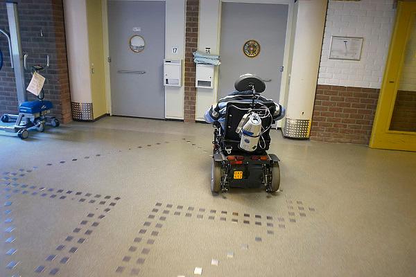 Nederland, Arnhem, 22-11-2012Gehandicapte man in zijn scootmobiel in de gang van een verzorgingshuis. Hij heeft een zuurstoffles achterop.Foto: Flip Franssen