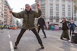 A man dances in the early morning light on Oxford Street as hundreds of environmental protesters from Extinction Rebellion occupy Marble Arch, camping in the square and even on the streets, blocking access to traffic on Park Lane and Oxford Street in London's usually traffic-heavy west end. . London, April 16 2019.