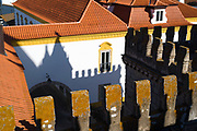 Crenellations and shadows of the Se Cathedral tower on typical yellow and white buildings  in Evora, Portugal