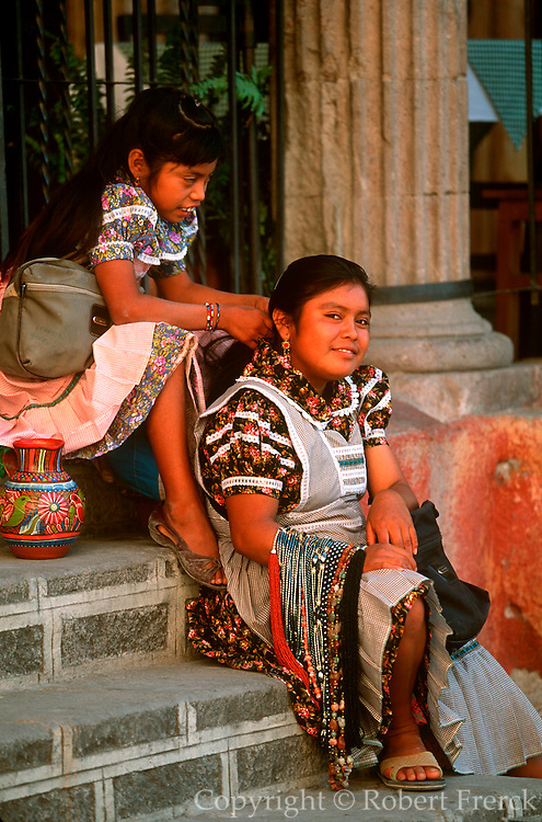 MEXICO, COLONIAL CITIES, GUANAJUATO San Miguel de Allende, two girls waiting on steps in old market in the Zocalo