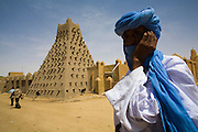 A man wearing tuareg clothing talks on the phone in front of Sankoré Mosque, in Timbuktu, Mali.