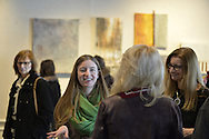 """Roslyn, New York, USA. January 31, 2015. Ellen Hallie Schiff, at extreme right, speaks with visitors at Artists Reception for """"The Alchemists"""" at Bryant Library. Schiff curated the exhibition, which included artwork of five artists, including herself."""