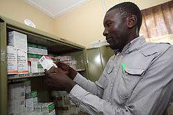 Pharmacist... Uses his smartphone and computer to work on needs and cases from his desk. SAHFA baseline survey visit to Angiya, Homa Bay County, Kenya.  SAHFA Kenya © April 2019