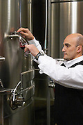 Juan Gustavo Agostini, winemaker and oenologist, taking a sample from a stainless steel fermentation tank. Bodega NQN Winery, Vinedos de la Patagonia, Neuquen, Patagonia, Argentina, South America