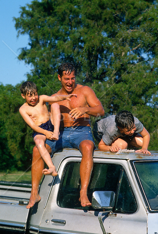 two boys and man being sprayed with water while they are on top of a truck