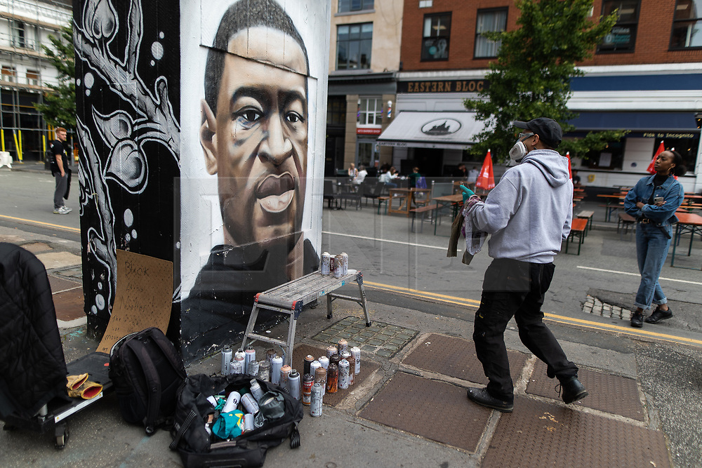 """© Licensed to London News Pictures . 22/07/2020 . Manchester , UK . A woman watches as a mural to George Floyd in the Northern Quarter of Manchester City Centre is repainted by the artist after it was sprayed with racist graffiti . """" Nigger """" was sprayed across the face of the artwork by Manchester artist AKSE overnight . Photo credit : Joel Goodman/LNP"""