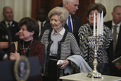Holocaust survivors walk up the stage as President Donald Trump speaks during a Hanukkah reception in the East Room of the White House on December 6, 2018 in Washington, DC. Behind Trump, Vice President Mike Pence. (Photo by Oliver Contreras/SIPA USA)