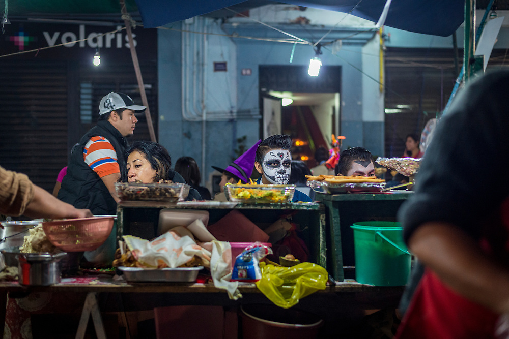 Oaxaca, Mexico - November 1, 2014: A young man with face paint waits for his food at a street food stall in an alley beside the Zócalo during Day of the Dead (Dia de los Muertos) festivities in Oaxaca, Mexico.