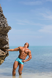 muscular man with a great body standing in the Atlantic Ocean near a Coral cliff in Bermuda