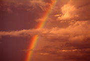An orange sky with clouds and a rainbow.