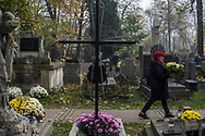 A woman walks with a bouquet of flowers in her hand on the Rakowicki Cemetery in Krakow, Poland 2019.