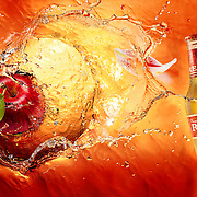 Apples falling into liquid creating a splash. Bottle of Redd's Cider, petals and leaves Ray Massey is an established, award winning, UK professional  photographer, shooting creative advertising and editorial images from his stunning studio in a converted church in Camden Town, London NW1. Ray Massey specialises in drinks and liquids, still life and hands, product, gymnastics, special effects (sfx) and location photography. He is particularly known for dynamic high speed action shots of pours, bubbles, splashes and explosions in beers, champagnes, sodas, cocktails and beverages of all descriptions, as well as perfumes, paint, ink, water – even ice! Ray Massey works throughout the world with advertising agencies, designers, design groups, PR companies and directly with clients. He regularly manages the entire creative process, including post-production composition, manipulation and retouching, working with his team of retouchers to produce final images ready for publication.