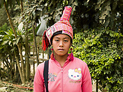 Portrait of a Ko Pala ethnic minority woman wearing a traditional headdress and Hello Kitty modern sweatshirt at Pak Nam Noi market, Phongsaly Province, Lao PDR. One of the most ethnically diverse countries in Southeast Asia, Laos has 49 officially recognised ethnic groups although there are many more self-identified and sub groups. These groups are distinguished by their own customs, beliefs and rituals. Details down to the embroidery on a shirt, the colour of the trim and the type of skirt all help signify the wearer's ethnic and clan affiliations.
