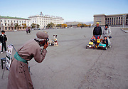 A photographer takes souvenir photographs to sell to visitors in Sukhbaatar Square, in the center of Ulaanbaatar, Mongolia. Sukhbaatar is Mongolia's national hero who liberated Mongolia from Chinese rule. Parliament buildings are in the background. Material World Project.
