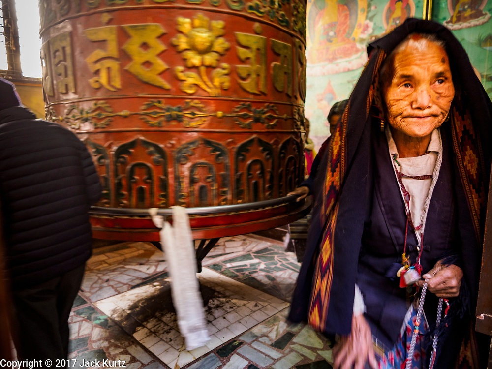 17 MARCH 2017 - KATHMANDU, NEPAL: A woman leaves a prayer wheel room at a monastery in front of Boudhanath Stupa in Kathmandu. The stupa is the holiest site in Nepali Buddhism. It is also the center of the Tibetan exile community in Kathmandu. The Stupa was badly damaged in the 2015 earthquake but was one of the first buildings renovated.     PHOTO BY JACK KURTZ