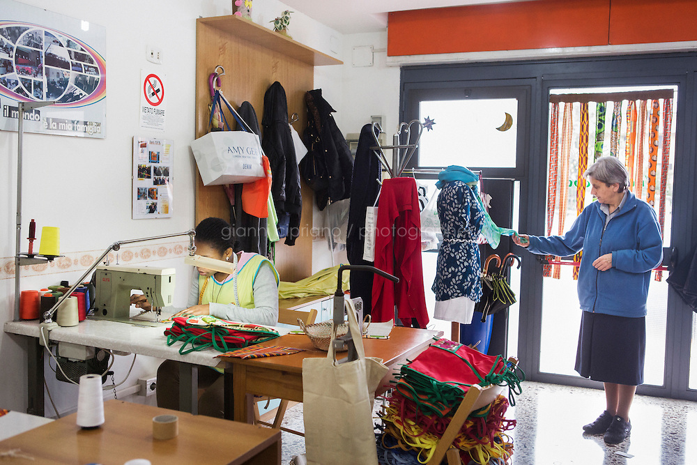 CASERTA, ITALY - 25 FEBRUARY 2015: A Nigerian immigrant woman and ex-sex worker sews fabrics for an arm chair caddy, as Sister Giaretta checks a handmade scarf at the New Hope tailor's shop in Caserta, Italy, on February 25th 2015.<br /> <br /> New Hope is an ethnic tailor's shop that makes a variety of colourful products working mainly african fabrics. The New Hope social cooperative, founded in 2014, promotes a training workshop for your immigrant women, many of which have children, that want to integrate in Italian society.