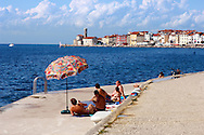 Friends with their umberella sunbathing and talking. Piran , Slovenia Visit our PHOTO COLLECTIONS OF SLOVANIAN  HISTOIC PLACES for more photos to download or buy as wall art prints https://funkystock.photoshelter.com/gallery-collection/Pictures-Images-of-Slovenia-Photos-of-Slovenian-Historic-Landmark-Sites/C0000_BlKhcYWnT4Sites/C0000qxA2zGFjd_k