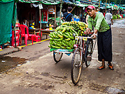 22 NOVEMBER 2017 - YANGON, MYANMAR: A man pushes a bike load of bananas through a market in Yangon.     PHOTO BY JACK KURTZ