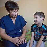 CAPTION: Dr Vera Shishkina talks Kirill through the procedure that will shortly be performed to close a fistula (gap) in his hard palate. She assures him that after the operation, it will be easier for him to talk, and also to eat as food is currently able to enter his nose. LOCATION: Volgograd City Hospital #1, Volgograd, Russia. INDIVIDUAL(S) PHOTOGRAPHED: Dr Vera Shishkina (left) and Kirill Fedorenko (right).