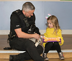 Four year old Heidi Wilkie from Prestonpans with new police dog puppy Sully and his handler PC Richard Smith, at the Royal Hospital for Sick Children in Edinburgh, where she was one of the patients who chose the names for 12 week old Springer Spaniels Banjo and Sully, the two newest members of Police Scotland's dog section. <br /> <br /> © Dave Johnston/ EEm