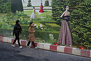 Hoarding outside a shop under refurbishment makes an interesting street scene on New Bond Street, London, UK. A weird visual juxtaposition is created as people integrate with the large scale printed photograph of women walking in a countryside garden.