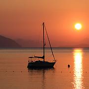 Beautiful sunrise in Aegean sea with boat and mountains, Turunc beach, Turkey