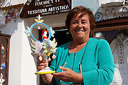 Trulli whistle shop La Botega die Finchietti, with owner Anna Marie  Matarrese holding an ornate folk decorated whistle.  Alberobello, Puglia, Italy.  Pictures, photos, images & fotos.