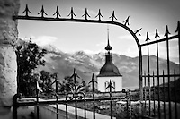 Black and white photo of an old fence outside of the Church of Gruyeres, Switzerland with a view of the alps in the background.