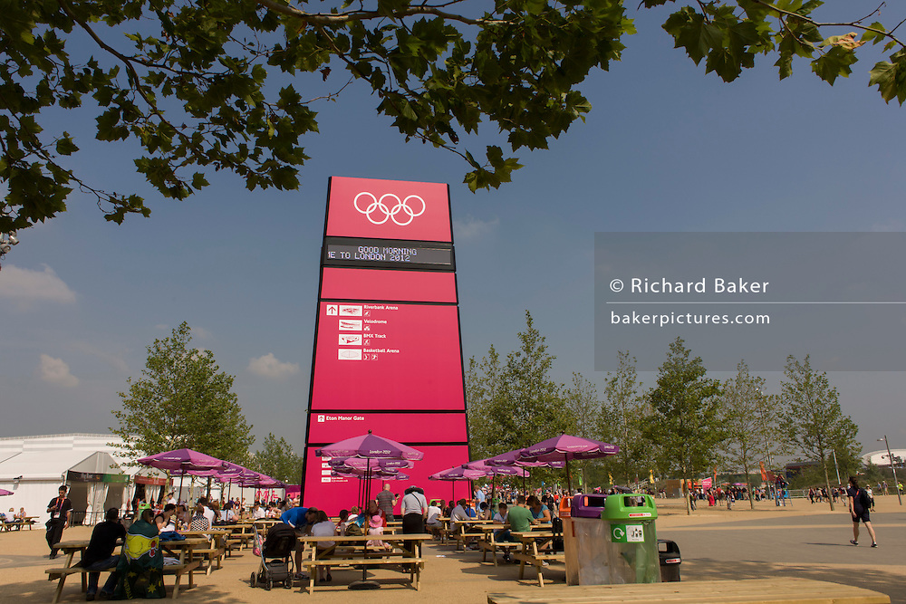 Spectators rest at tables and benches underneath a large welcoming gateway sign in the Olympic Park during the London 2012 Olympics. This land was transformed to become a 2.5 Sq Km sporting complex, once industrial businesses and now the venue of eight venues including the main arena, Aquatics Centre and Velodrome plus the athletes' Olympic Village. After the Olympics, the park is to be known as Queen Elizabeth Olympic Park.