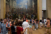 Tourists mingle beneath the Wedding at Cana (or The Wedding Feast at Cana), a massive painting by the late-Renaissance or Mannerist Italian painter, Paolo Veronese - on display in the Musée du Louvre in Paris, where it is the largest painting in that museum's collection.