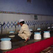 Student of the madrasa inside a small mosque in Old Delhi performing ablution