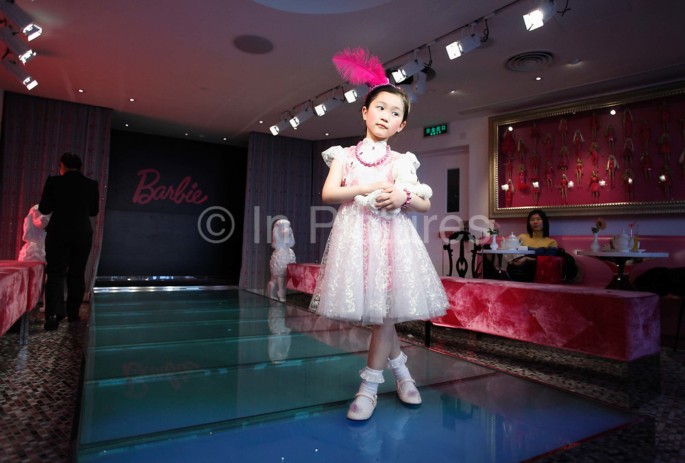 Young girls strut and pose on a small runway at the new Barbie flagship store in Shanghai, China on 04 April, 2009. The six story store was opened in March this year to mark the 50th birthday of Barbie. The Barbie store has become a hit in Shanghai as a place where doting mothers take their daughters, often the only child in the family, for a girls' day out..