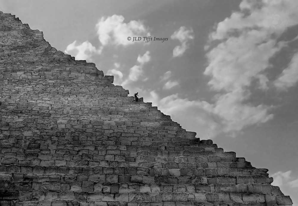 Great Pyramid, northeast corner, a boy descending the northeast corner edge is silhouetted against sky and puffy clouds.  In the 1970s people could, and did, frequently climb to the top of the Great Pyramid.