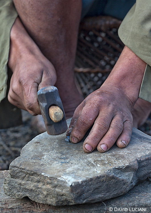 A man is shaping a bullet with a hammer.
