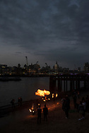 London, England - May 4, 2018: At dusk at Gabriel's Pier on the River Thames, young adults dance with fire, St. Paul's Cathedral visible in the background.