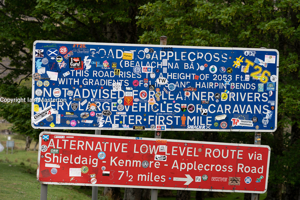 Road sign covered in stickers at foot of Applecross pass on the North Coast 500 tourist motoring route in northern Scotland, UK