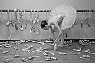 Ballerina poses with all the dancing shoes used during her career. Dancer: Manuelita Navarro.