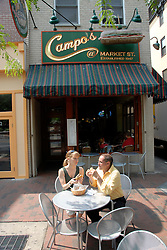 Couple eating at Campo's restaurant, outdoors, eating cheesesteaks, mod rel..Philadelphia, Pennsylvania, PA USA.  Photo copyright Lee Foster, 510-549-2202, lee@fostertravel.com, www.fostertravel.com.  Photo 338-30279