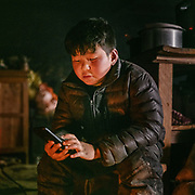 Karma is playing on his phone. Life at Mr and Ms Wangchuk's house on the edge of the Laya village.