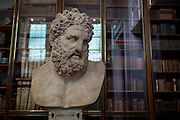 The bust of mythical Hercules, a Roman copy of the ancient Greek original by Lysippos (of about 325-300BC) in the Enlightenment Gallery of the British Museum on 28th February 2017, in London, England. The Roman version is said to have been found in lava at the foot of Vesuvius and presented to the museum by Sir William Hamilton in 1776. Hercules is the Roman adaptation of the Greek divine hero Heracles,  the son of Zeus (Roman equivalent Jupiter) and the mortal Alcmene. In classical mythology, Hercules is famous for his strength and for his numerous far-ranging adventures.