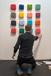 © Licensed to London News Pictures. 16/01/2018. LONDON, UK. A staff member hangs a selection of coloured bricks by Muirne Kate Dineen. Preview day of the 30th anniversary of the London Art Fair.  The fair launches the international art calendar with modern and contemporary art from leading galleries around the world and is taking place at the Business Design Centre, Islington from 17 to 21 January 2018.   Photo credit: Stephen Chung/LNP
