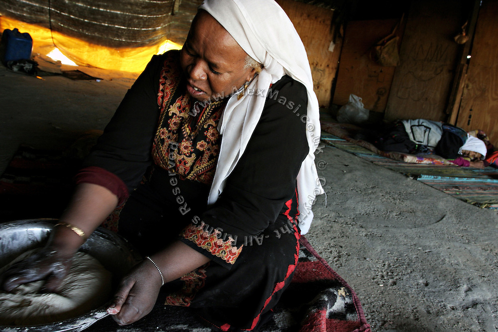 Khandra, a 55-year-old Bedouin woman, is making the bread in her house in the unrecognised village of Wadi el Na'am, pop. 4000, close to Beer Sheva, the capital of the Negev, a large deserted area in the south of Israel.  Wadi el Na'am is located near a large industrial site, Ramat Hovav, and has no infrastructure or electric energy. Water is provided only via storage tanks. It has no health services as the only clinic is deemed illegal and bound to be demolished, as the rest of the structures in the area. Numbering around 200.000 in Israel, the Bedouins constitute the native ethnic group of these areas, they farm, grow wheat, olives and live in complete self sufficiency. Many of them were in these lands long before the Israeli State was created and their traditional lifestyle is now threatened by subtle Governmental policies. The seven Bedouin towns already built are all between the 10 more impoverished towns in Israel. ..