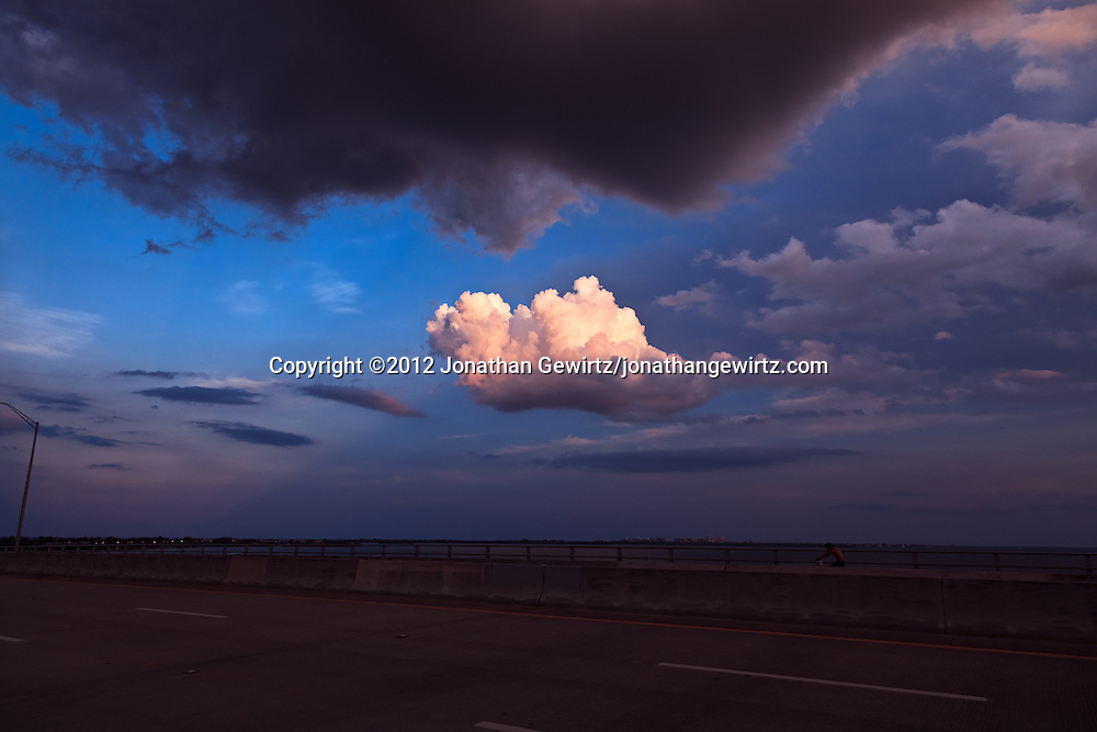 A solitary cloud over Key Biscayne is illuminated by the setting sun in this view from the top of the William Powell bridge, part of Miami's Rickenbacker Causeway. WATERMARKS WILL NOT APPEAR ON PRINTS OR LICENSED IMAGES.