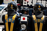Policemen in riot gear man a road block to stop the sound trucks of the paramilitary Uyoku Dantai right wing groups outside Yasukuni Shrine. On August 15th every year people gather at Yasukuni Shrine to commemorate the end of the Pacific War. Notionally a call for remembrance and continued peace it is also a Mecca for right wing nationalist including  the paramilitary Uyoku Dantai. Tokyo, Japan, August 15th 2009